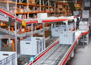 Automatisches Lagerhaus. Schachteln mit Ersatzteilen, die auf dem Förderer angebracht werden